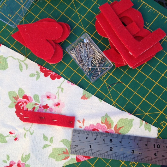 Tacking letter embellishments onto the pennants